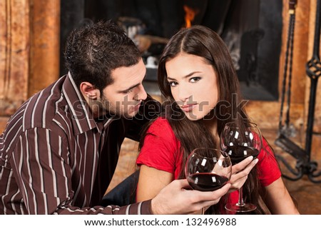 Young couple in love near fireplace - stock photo