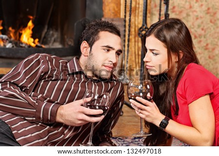 Young couple in love near fireplace holding glass of wine, focus on woman - stock photo