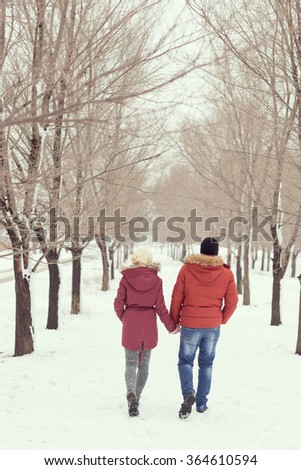 Young couple in love on a winter holiday walking away of the camera, holding hands