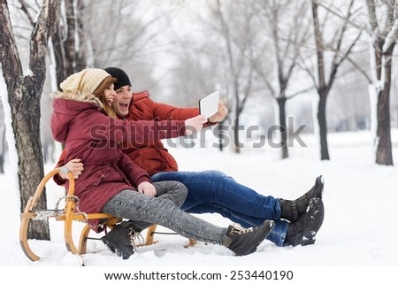 Young couple in love on a winter vacation sitting on a sleigh and making selfie - stock photo