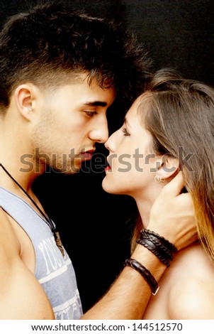 Young couple in love on black background