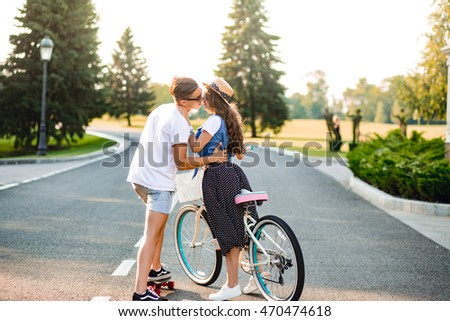 Young couple in love on road on sunset. Pretty girl with long curly hair in hat and long skirt holds a bike, handsome guy on skateboard hugging and going to kiss her.