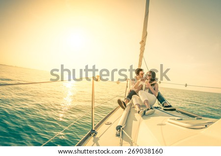 Young couple in love on sail boat with champagne at sunset - Happy exclusive alternative lifestyle concept  - Soft focus due to backlight on vintage nostalgic filter - Fisheye lens and tilted horizon - stock photo