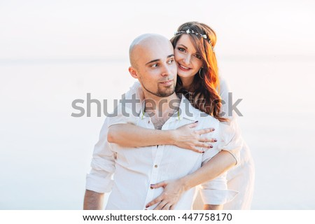 Young couple in love on summer sunny evening on the sea - stock photo
