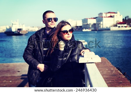 Young couple in love outdoor. Fashion portrait of pretty stylish young sensual couple in cold winter weather and have fun together.  - stock photo
