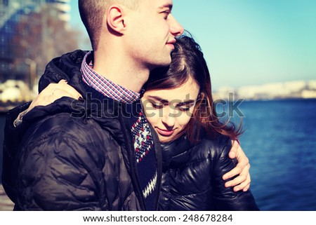 Young couple in love outdoor. Fashion portrait of pretty stylish young sensual couple in cold winter wather and have fun together.  - stock photo