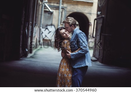 Young couple in love outdoor.  Man hugs  woman. kiss on the forehead - stock photo