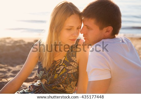 Young couple in love outdoor. Portert of young beautiful couple on the beach in the sunset sun. - stock photo