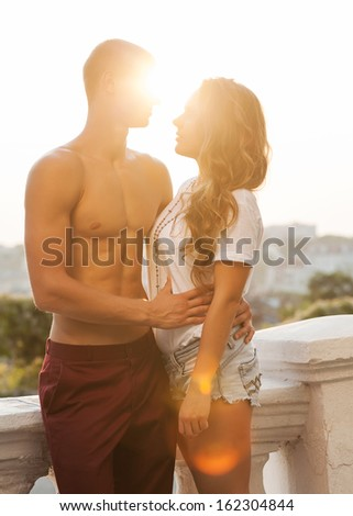 Young couple in love outdoor. Romantic young couple enjoying sun, sunshine, romance and love. - stock photo