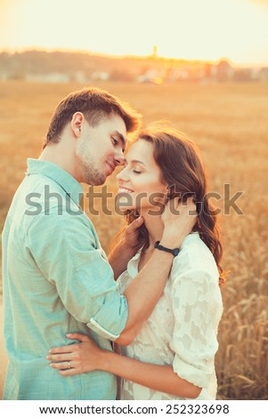 Young couple in love outdoor.Stunning sensual outdoor portrait of young stylish fashion couple posing in summer in field.Happy Smiling Couple in love.They are smiling and looking at each other - stock photo
