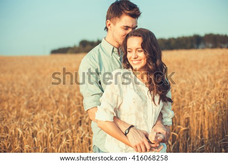 Young couple in love outdoor. Stunning sensual outdoor portrait of young stylish fashion couple posing in summer in field. Happy Smiling Couple in love. They are smiling and looking at each other - stock photo