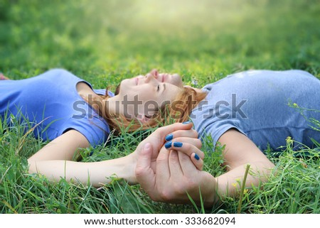 Young couple in love outdoors holding hands, lying down on meadow beautiful girl with boyfriend relax in park closing their eyes  - love affection  and tenderness concept -  tight focus on hands - stock photo