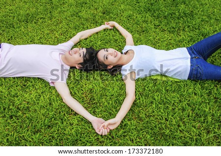 Young couple in love outdoors on grass - stock photo