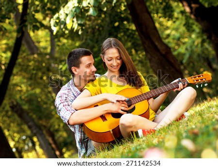 Young couple in love playing acoustic guitar in the park  - stock photo