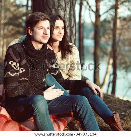 Young couple in love posing in winter forest  - stock photo