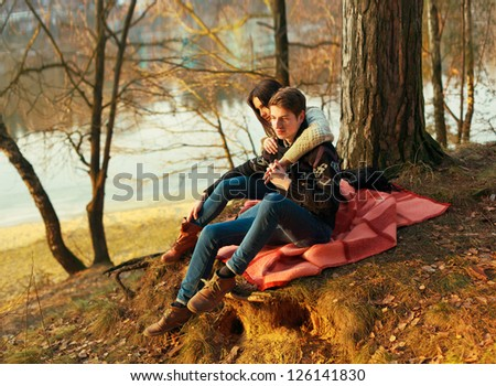 Young couple in love posing in winter. Sensual boy and girl sitting on the ground in spring park - stock photo