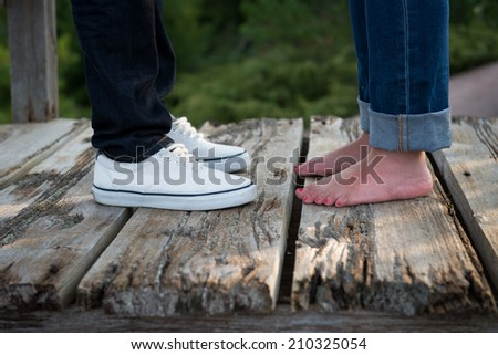 Young couple in love put toes together - stock photo