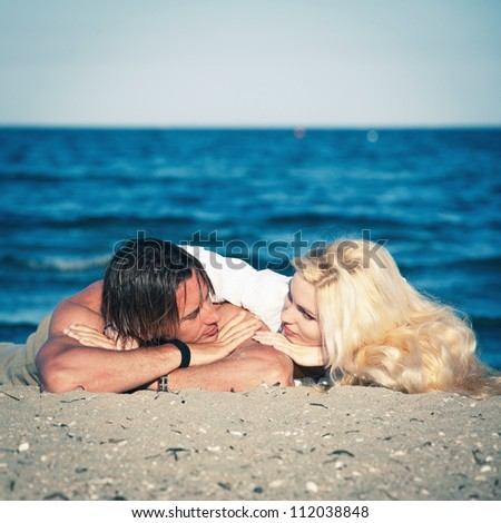 Young couple in love relaxing at the beach. - stock photo