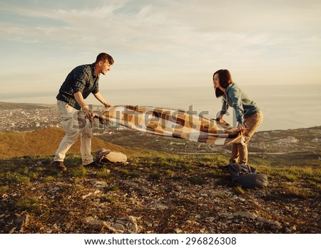 Young couple in love resting on peak of mountain in summer. Couple spreading a blanket for picnic