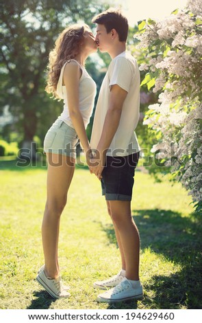 Young couple in love, sensual kiss in sunny summer day - stock photo