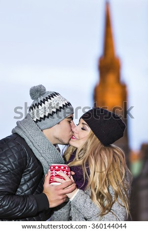Young couple in love share hot drink in red cup on Royal Mile in Edinburgh. Two youngsters dating on Valentine's day. Boyfriend kisses his girlfriend. - stock photo