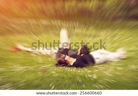 Young couple in love sharing intimate romantic moment - man laying with his head on girl's thigh, with love and emotions. Radial zoom effect defocusing filter applied, with vintage instagram look. - stock photo