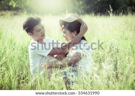 Young couple in love sitting and look each other in the meadow in green vintage color filter