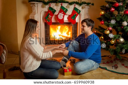 Young couple in love sitting at fireplace and holding hands