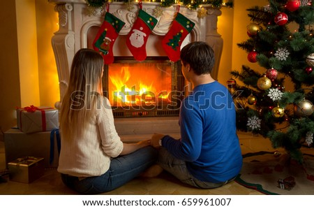 Young couple in love sitting by the fireplace decorated or Christmas and looking at fire