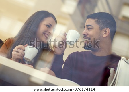 Young couple in love sitting in a cafe and communicating - stock photo