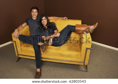Young couple in love sitting on couch - stock photo