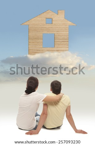Young couple in love smiling happy together sitting on floor thinking and imaging their new house - stock photo