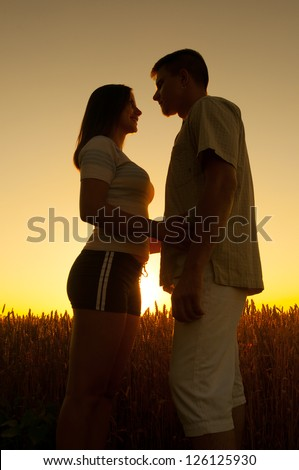 Young couple in love standing in the wheat field at sunset on beautiful summer day. - stock photo