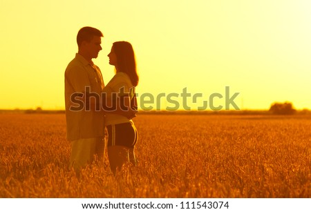 Young couple in love standing in the wheat field on sunny summer day. - stock photo