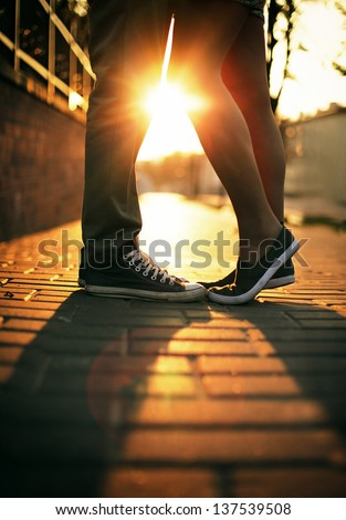 Young couple in love standing on the street in gumshoes in summer sunny warm weather. - stock photo