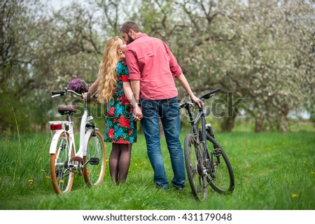 Young couple in love standing with the bicycles back to camera, holding hands and kissing each other in the spring garden, against the background of trees and fresh greenery.