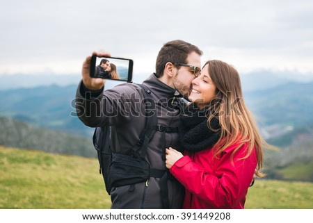 Young couple in love  taking selfie while kissing, hiking outdoor on vacation. Rural holyday relaxing gateaway. - stock photo