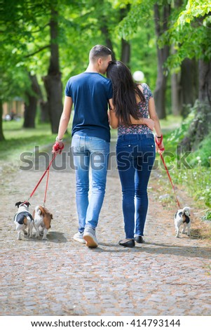 Young couple in love,walking and enjoy in park with his dogs.(Under exposed and colored photo)