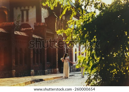 Young couple in love walking in the autumn park holding hands near old town - stock photo