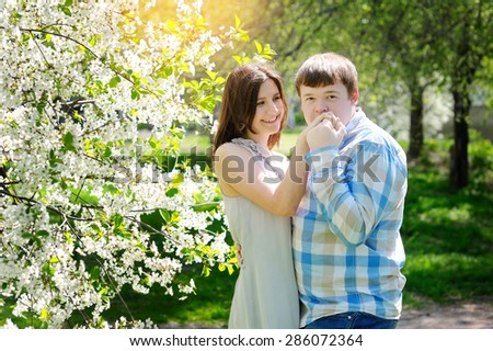 young couple in love walking in the blossoming spring garden.