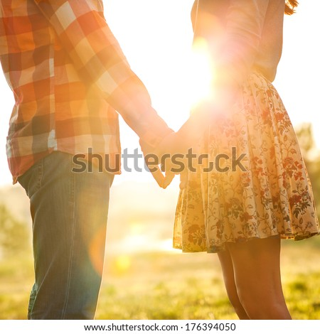 Young couple in love walking in the park holding hands looking in the sunset.concept of Valentine's Day. - stock photo