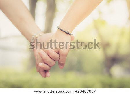 Young couple in love walking in the park holding hands , selective focus , copy space , vintage tone.
