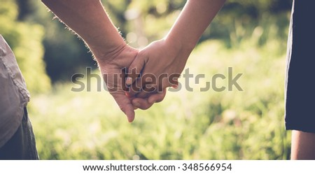 Young couple in love walking in the summer park holding hands, filtered image - stock photo