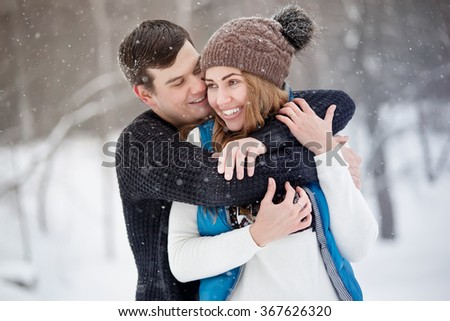 Young couple in love walking in winter park. It's snowing, winter. Young man embraces the girl. She laughs. - stock photo