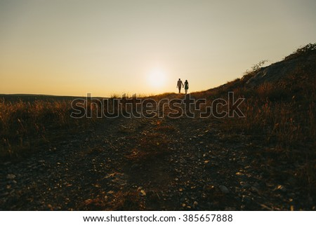 Young couple in love walking outdoor holding hands in the sunset - stock photo