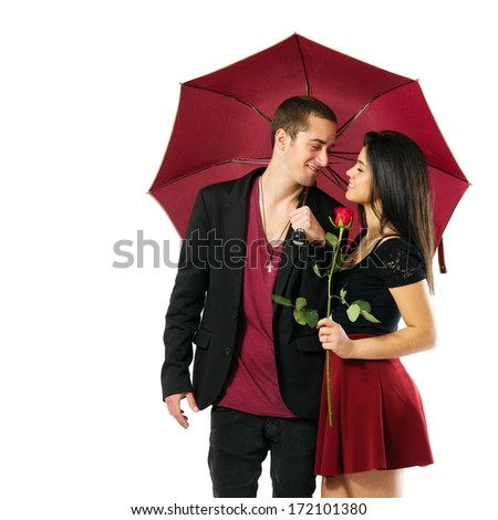 Young couple in love with red umbrella and flower over white background - stock photo