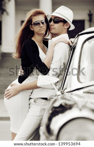 Young couple in love with retro car - stock photo