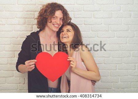 Young couple in love. Young man and woman embracing and holding red paper heart - symbol of love. Image toned and noise added. - stock photo