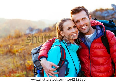 Young couple in mountains smiling - stock photo
