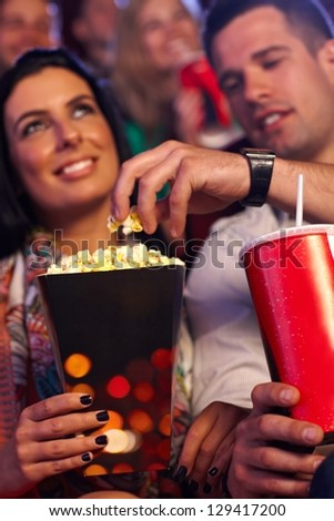 Young couple in multiplex movie theater, eating popcorn. Focus on hands and popcorn. - stock photo